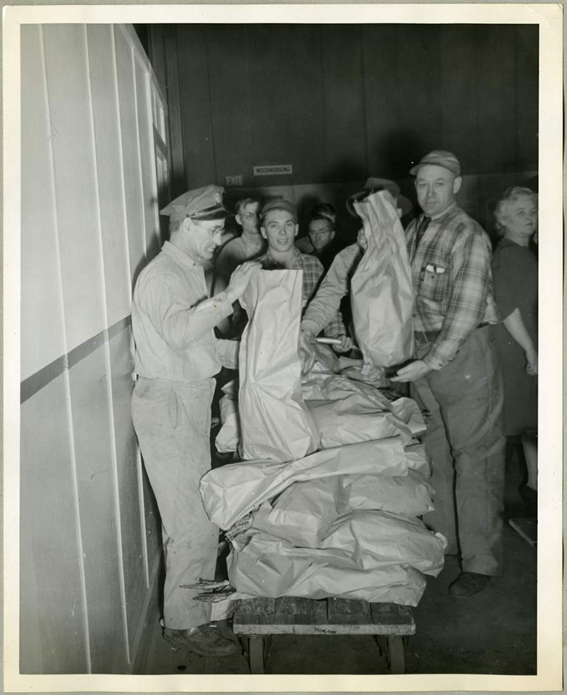 Employees of the Northwestern Aeronautical Corporation stand in line to receive their bagged, holiday turkeys.
